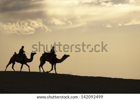 JAISALMER, INDIA - FEB 26: Two cameleers go through the Thar Desert, on Feb 26, 2013 in Jaisalmer, India.  Apart from farming, camel riding activity is another income source for desert villagers - stock photo