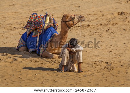 Jaisalmer, India - February 25, 2013: Cameleer at the Sam Sand Dune. Camel riding activity for tourists is another income source for desert villagers apart from farming and animal raising