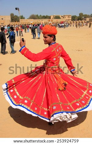 JAISALMER, INDIA - FEBRUARY 16: Unidentified man dances during Desert Festival on February 16, 2011 in Jaisalmer, India. Main purpose of Festival is to display rich and colorful culture of Rajasthan - stock photo