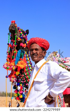 JAISALMER, INDIA - FEBRUARY 16: Unidentified man leads camel during Desert Festival on February 16, 2011 in Jaisalmer, India. Main purpose of Festival is to display colorful culture of Rajasthan