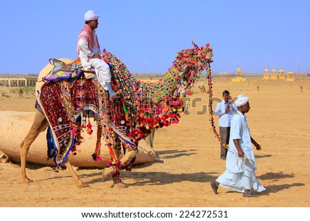 JAISALMER, INDIA - FEBRUARY 17: Unidentified man rides camel during Desert Festival on February 17, 2011 in Jaisalmer, India. Main purpose of Festival is to display colorful culture of Rajasthan