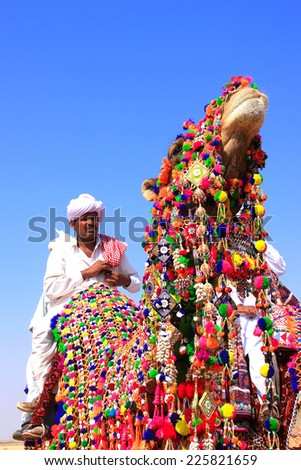JAISALMER, INDIA - FEBRUARY 17: Unidentified man rides camel during Desert Festival on February 17, 2011 in Jaisalmer, India. Main purpose of Festival is to display colorful culture of Rajasthan - stock photo