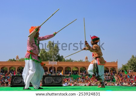 JAISALMER, INDIA - FEBRUARY 16: Unidentified men dance during Desert Festival on February 16, 2011 in Jaisalmer, India. Main purpose of Festival is to display rich and colorful culture of Rajasthan - stock photo
