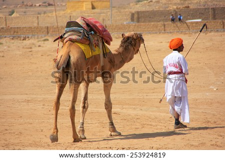 JAISALMER, INDIA-FEBRUARY 16: Unidentified polo player leads camel during Desert Festival on February 16, 2011 in Jaisalmer, India. Main purpose of Festival is to display colorful culture of Rajasthan - stock photo
