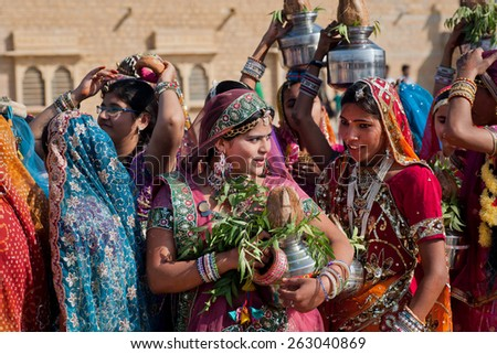 JAISALMER, INDIA - MAR 1: Asian women gossiping in the crowd of friends during a campaign of the famous Desert Festival on March 1, 2015. Every winter Jaisalmer takes the Desert Festival of Rajasthan - stock photo