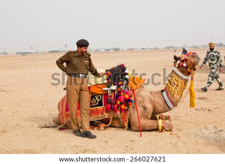 JAISALMER, INDIA - MAR 1: Indian police man holding the camel before the show of the Desert Festival on March 1, 2015 in Rajasthan. Every winter Jaisalmer takes the Desert Festival