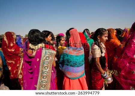 JAISALMER, INDIA - MAR 1: Many colorful women in sari standing in crowd before the presentation on the Desert Festival on March 1, 2015 in Rajasthan. Every winter Jaisalmer takes the Desert Festival - stock photo