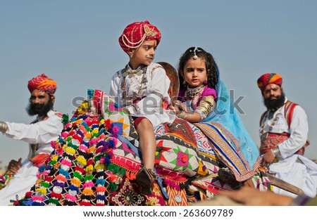JAISALMER, INDIA - MAR 1: Unidentified boy and girl ride on a camel in the crowd of soldiers Rajasthan during the Desert Festival on March 1 2015. Every winter Jaisalmer takes famous Desert Festival - stock photo