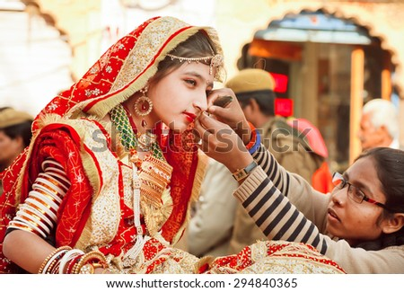 JAISALMER, INDIA - MAR 1: Unidentified girl with golden jewelry and traditional saree takes help from mother during the Desert Festival on March 1, 2015. Every winter Jaisalmer takes Desert Festival - stock photo