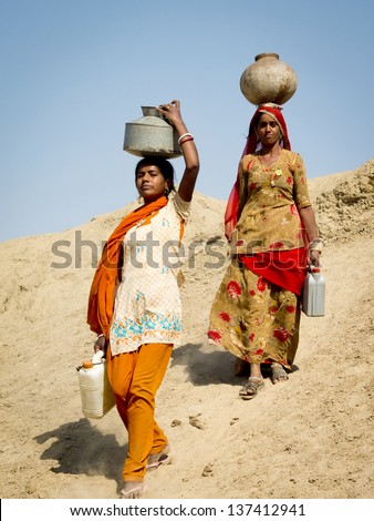 JAISALMER,  INDIA - MARCH 8: Close-up portrait of two women carrying  water in the desert , on March 8, 2013, Jaisalmer, India. They are walking on a dune with heavy jugs on their heads.