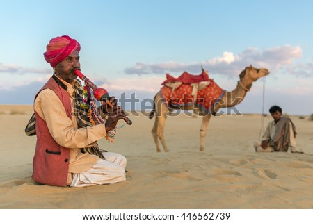 Jaisalmer, India - March 13, 2016: Unidentified man plays traditional music after camel ride in Thar desert near Jaisalmer, India.