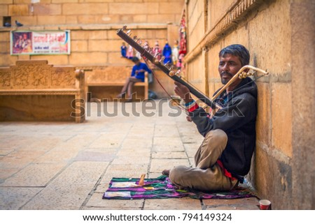 Jaisalmer, Rajasthan, India - December 5 2017 : A street artist earning his daily living by playing Rajasthani folk music