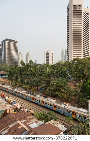 JAKARTA, INDONESIA - AUGUST 21 2015: A commuter train goes through a shanty town right next to the business district of Jakarta, where poverty contrasts with modern office in the background.