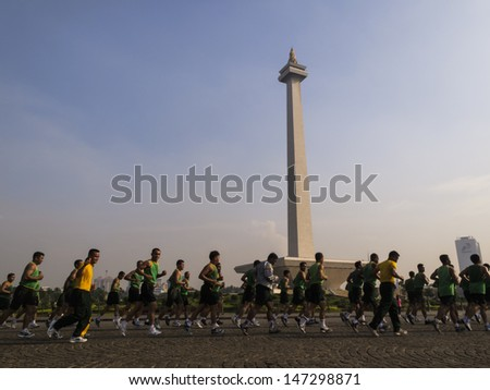 JAKARTA, INDONESIA - DECEMBER 10:  View of many men running around the National Monument on December 10, 2009 in Merdeka Square Jakarta, Indonesia which was rededicated July 23, 2013 by the President - stock photo