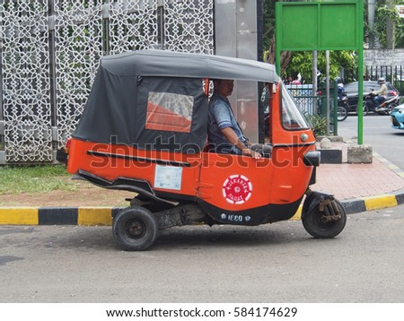 Jakarta,  Indonesia - January 11, 2015: Orange, three-wheeled car with a driver driving down the road in  Jakarta.