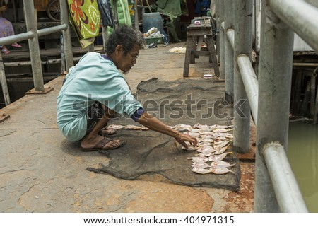 Jakarta, Indonesia - March 16, 2016:  Fisherman considers dried fish on a tray. Sunda Kelapa old Harbour with fishing boats, ship and docks in Jakarta, Indonesia.