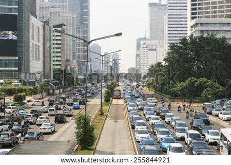 Jakarta, Indonesia - May 04 2013: A Transjakarta runs along its reserved lane in busy traffic in the middle of Jakarta, a city known for traffic congestion.