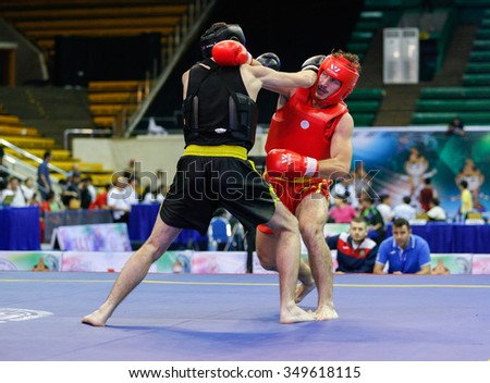 JAKARTA, INDONESIA - NOVEMBER 15, 2015: Alessandro Cutuli of Italy (red) fights Aleksandr Yudin of Ukraine (black) in the men's 70kg Sanda event at the 13th World Wushu Championship 2015.
