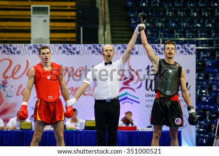 JAKARTA, INDONESIA - NOVEMBER 17, 2015: Andrei Nedikov of Belarus (red) loses to Gary Chandler of the USA (black) in the men's 65kg Sanda event at the 13th World Wushu Championship 2015. - stock photo