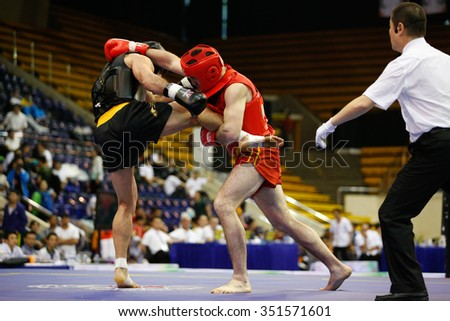 JAKARTA, INDONESIA - NOVEMBER 17, 2015: Arsian Bektemirov of Russia (red) fights Amir Fazli of Iran (black) in the men's 85kg Sanda semi-final event at the 13th World Wushu Championship 2015. - stock photo