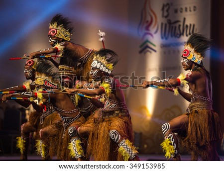 JAKARTA, INDONESIA: NOVEMBER 13, 2015: Dancers perform a traditional Papua warrior dance at the opening ceremony of the 13th World Wushu Championship 2015 in Jakarta Convention Centre. - stock photo