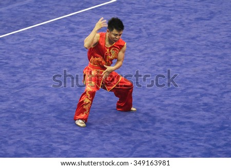 JAKARTA, INDONESIA: NOVEMBER 14, 2015: Friday Nnadi from Nigeria performs the movements in the men's Nanquan event at the 13th World Wushu Championship 2015 in Istora Senayan, Jakarta. - stock photo