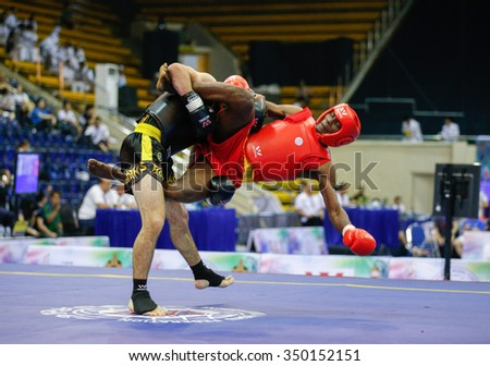 JAKARTA, INDONESIA - NOVEMBER 16, 2015: Rodrigue Koto of Benin (red) fights Fardin Javanmard of Switzerland (black) in the men's 70kg Sanda event at the 13th World Wushu Championship 2015. - stock photo