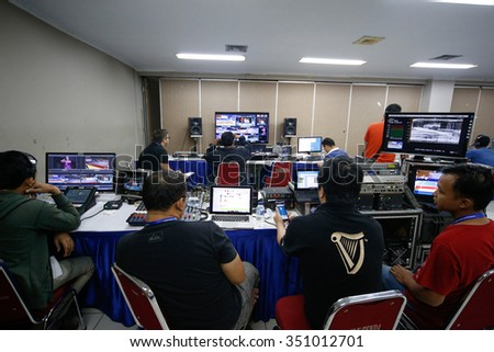 JAKARTA, INDONESIA - NOVEMBER 16, 2015: Wushu TV broadcast crew works in the master control room to provide live streaming telecast of all the events at the 13th World Wushu Championship 2015. - stock photo
