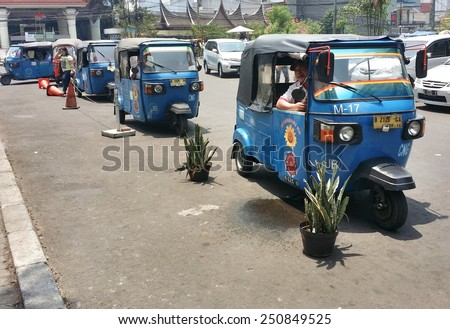 JAKARTA, INDONESIA - SEPT 13, 2014 : Public transport 'tuktuk' wait for passangers in Jakarta, Indonesia. This type of transport is widely preferred in this congested city. - stock photo