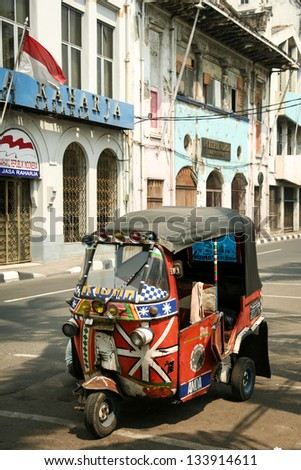 JAKARTA - SEPTEMBER 22: tuk tuk motorized rickshaw cheap form of public transport parked outside old colonial era buildings on September 22 2007 in Jakarta. - stock photo