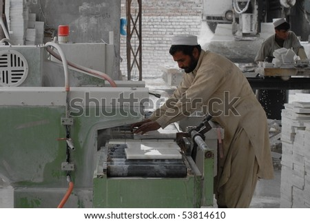 JALALABAD - JANUARY 27: Mirwais, 40, from Jalalabad, Nangharhar, runs water over polished marble at marble factory January 27, 2010 in Jalalabad, eastern Afghanistan.