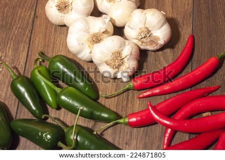 Jalapeno, chili and garlic, on wooden background - stock photo