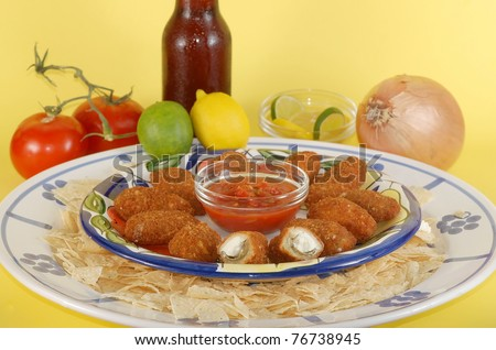 Jalapeno poppers on blue and white, hispanic design platter with spicy salsa and tortilla chips and ice-cold beer; surrounded by mexican food ingredients and isolated against bright yellow background.