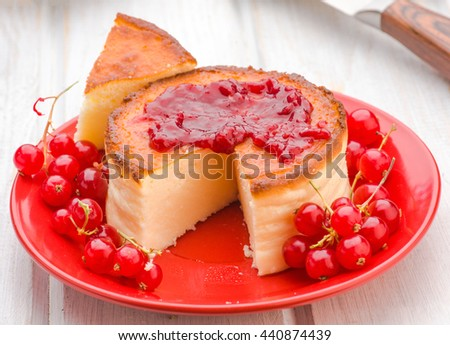 jam and cheesecake with currants on wooden table
