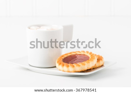 Jam filled cookies served with hot chocolate. - stock photo