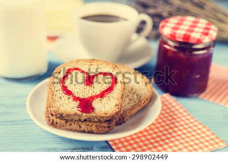 jam forming a heart on a toast, on a rustic blue wooden table, with a cross-process effect - stock photo