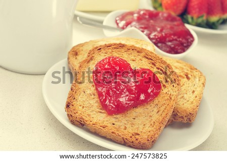 jam forming a heart on a toast, on a set table for breakfast - stock photo