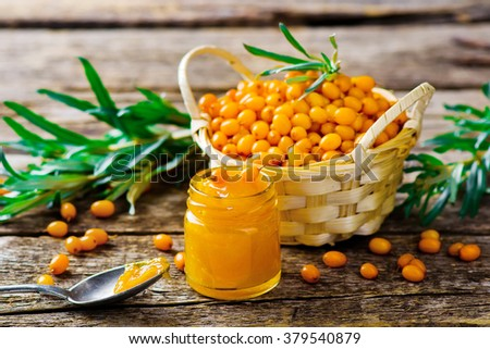jam from a sea-buckthorn and berry of an organic sea-buckthorn in a basket. style rustic . selective focus - stock photo