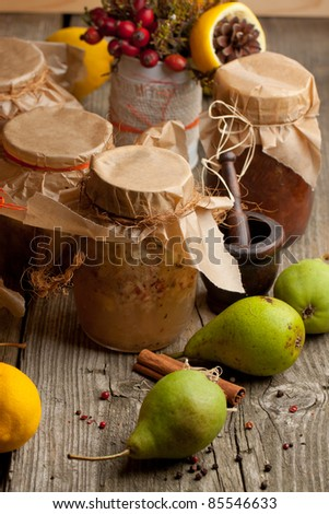 Jam in jars and fresh pears and lemon on old wooden table - stock photo