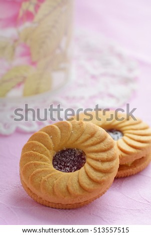 Jam shortbread cookies with floral mug in vertical format.  Very shallow depth of field with focus on jam center of cookie. Room for text.