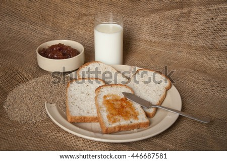 Jam spread on a slice of bread with more bread slice, a bowl of jam, glass of milk and heap of celery in the background