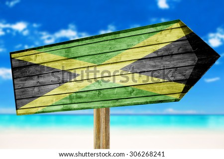 Jamaica flag wooden sign with on a beach background - stock photo