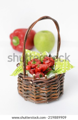 Jamaican red hot peppers in a basket on white background, vertical composition. - stock photo