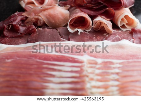 Jambon mix. Ham. Traditional Italian and Spanish salting, smoking, dry-cured dish - jamon Serrano and prosciutto crudo sliced, background. Copy space. Closeup.