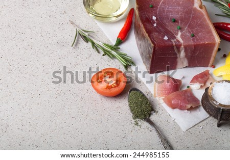 Jamon with herbs and spices, salt, olive oil and tomatoes on stone background. - stock photo