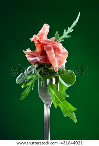jamon with spinach and  arugula on green background - stock photo