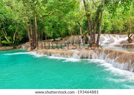 Jangle landscape with amazing turquoise water of Kuang Si cascade waterfall at tropical rain forest near Luang Prabang, Laos - stock photo