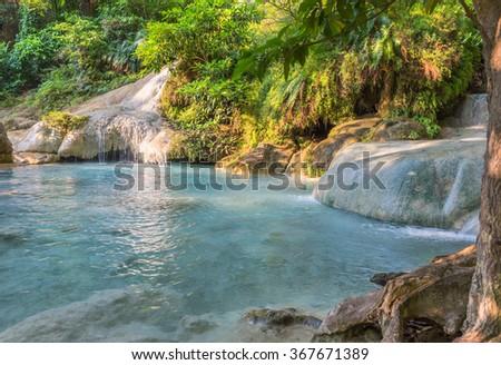 Jangle landscape with flowing turquoise water of seven step Erawan cascade waterfall at deep tropical rain forest. Erawan Falls National Park at Kanchanaburi, Thailand - stock photo
