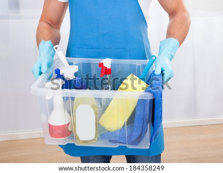 Janitor or cleaner wearing an apron and gloves carrying a tub of cleaning supplies as he goes about his work at the office - stock photo