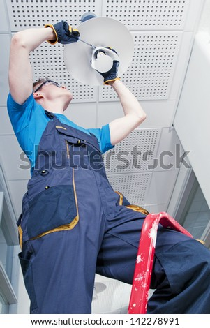 Janitor repairing broken lamp in corridor - stock photo